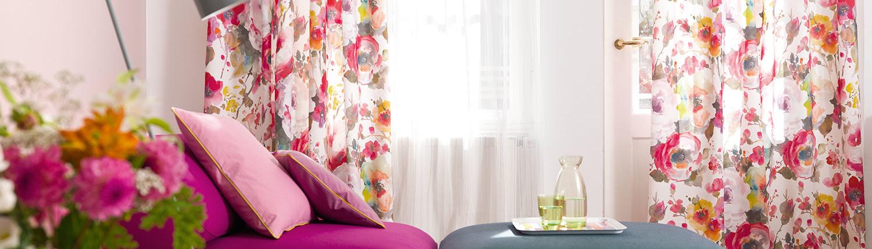 Modernes buntes Sofa mit geblümten Stores im Hintergrund