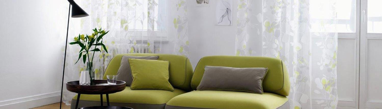 Grünes Sofa mit luftigen Vorhängen im Hintergrund