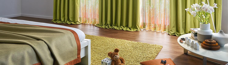 Schlafzimmer mit grünen Stores und Holzfußboden