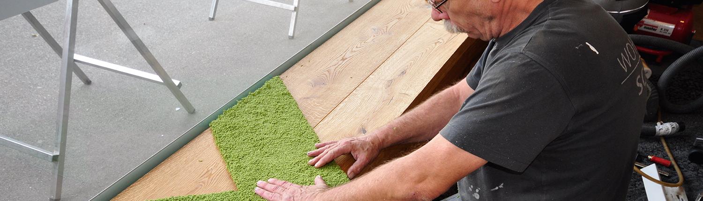 Mitarbeiter beim verlegen von Teppichboden auf einem Absatz